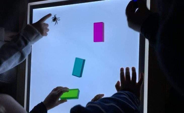 kinder legen farben auf leuchttisch